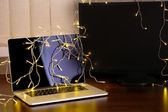 Laptop with garland, on office interior background — Stockfoto