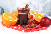 Fragrant mulled wine in glass on napkin on winter background — Stock Photo