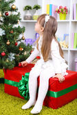 Little girl setting on big present box near Christmas tree in room — 图库照片