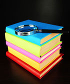 Color books with magnifying glass on table on black background — Stock Photo