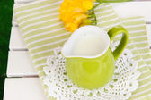 Green jug with milk on napkin on wooden picnic table close-up — Stock Photo