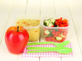 Tasty lunch in plastic containers, on wooden background — Stock Photo