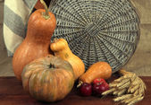 Pumpkins with apples and sheaf on wooden board on sackcloth background — Stock Photo