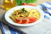 Ruddy fried potatoes on plate on wooden table close-up — Foto Stock