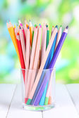 Colorful pencils in glass on wooden table on natural background — Foto de Stock