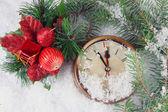 Uhr mit tanne äste und weihnachtsdekoration unter schnee hautnah — Stockfoto