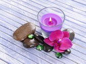 Beautiful colorful candles and orchid flower,on color wooden background — Stock Photo