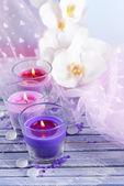 Piękne kolorowe świece i kwiaty orchidei, na drewnianym stole kolor, na jasnym tle — Zdjęcie stockowe