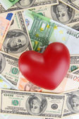 Love and money concept. Heart on European and American money — Stock Photo