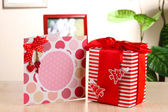 Gift with card on table on room background — Stock Photo