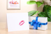 Gift with card for loved one on table on room background — Stock Photo