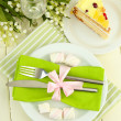 Table setting in white and green tones on color wooden background — Stock Photo