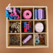 Stock Photo: Thread and materials for handiwork in box on brown background