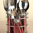 Knives, forks and spoons in metal stand on tablecloth on beige background — Stock Photo #37622043