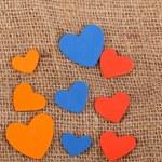 Hearts made of felt on sacking background — Stock Photo