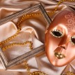 Stock Photo: Mask on golden fabric background
