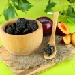 Fresh and dried plums in wooden bowl on napkin, on wooden background — Stock Photo
