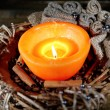 Burning candle with Christmas decorations on color wooden background — Stock Photo