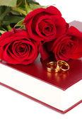 Обручальные кольца с розами на Библии, изолированные на белом фоне — Стоковое фото
