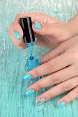 Mavi manikür, renkli arka plan üzerinde elleriyle güzel kadın — Stok fotoğraf