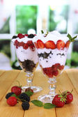 Natural yogurt with fresh berries on wooden table on green background — Stock Photo