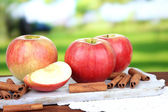 Ripe apples with with cinnamon sticks on wooden table, on bright background — Stock Photo