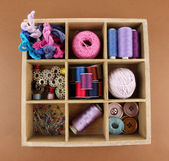 Thread and materials for handiwork in box on brown background — Stock Photo