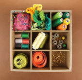 Thread and sewing tools in box on brown background — Stock Photo