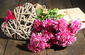 Bouquet of pink chrysanthemum letters and hearts on wooden table — Stockfoto