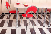 Modern red chairs near table in kitchen — Stock Photo