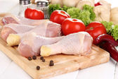 Raw chicken legs on wooden board close up — Stock Photo