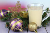 Cup of eggnog with fir branches and Christmas decorations on table on bright background — Foto de Stock