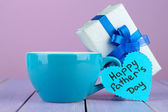 Happy Fathers Day tag with gift box and cup, on wooden table, on light background — Foto Stock