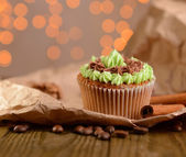 Tasty cupcake with butter cream, on wooden table, on lights background — Stock Photo