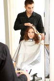 Young man hairdresser dyes hair girl in beauty salon — Stock Photo