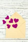 Schöne alte Umschlag mit dekorativen Herzen auf hölzernen Hintergrund — Stockfoto