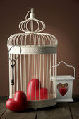 Hearts in decorative cage on wooden table, on brown background — Stock Photo