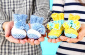 Hands with crocheted booties for baby, close-up — Stock Photo