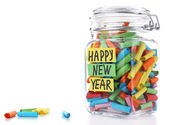 Dreams written on color rolled paper in glass jar, isolated on white — Stock Photo