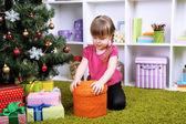 Little girl sitting near Christmas tree in room — 图库照片