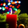 Composition with Burning candle, fir tree and Christmas decorations on multicolor lights background — Stok Fotoğraf #37655699