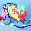 Sledge with Christmas presents, on blue background — Stock Photo