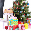 Female legs on wooden ladder near Christmas tree and gifts isolated on white — Stock Photo