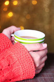 Hands holding mug of hot drink, close-up, on bright background — Stock Photo