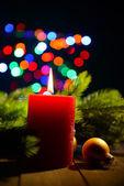 композиция с горящей свечи, дерево и рождественские украшения ели на фоне разноцветные огни — Стоковое фото