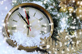 Clock with fir branches and Christmas decorations under snow close up — Stockfoto
