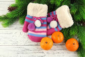Striped mittens with fir branches and tangerines on wooden background — Foto de Stock