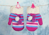 Striped mittens hanging on clothesline on bright background — 图库照片