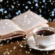 Composition of book with cup of coffee on table on dark background — Stock Photo