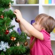 Little girl near Christmas tree in room — Stock Photo